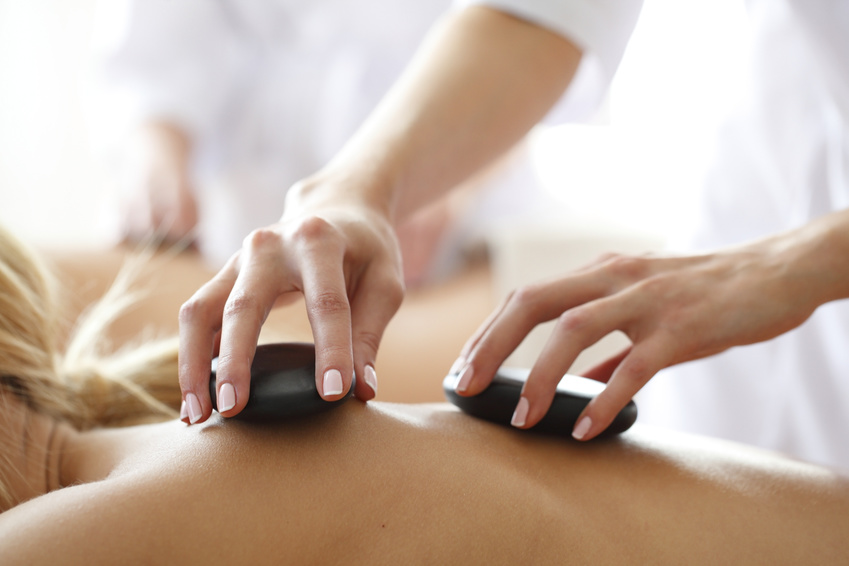 Young beautiful woman in spa getting hot stone massage